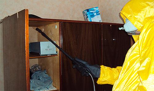 Дезинсектор обрабатывает квартиру от тараканов